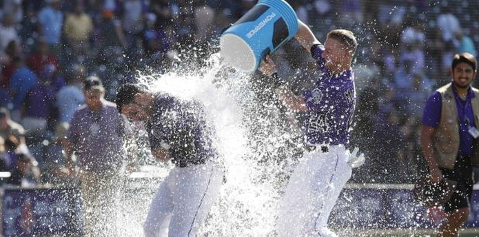 Nolan Arenado es 'bañado' por su compañero de equipo Ryan McMahon como parte de la celebración de la victoria de los Rockies. (AP /David Zalubowski)